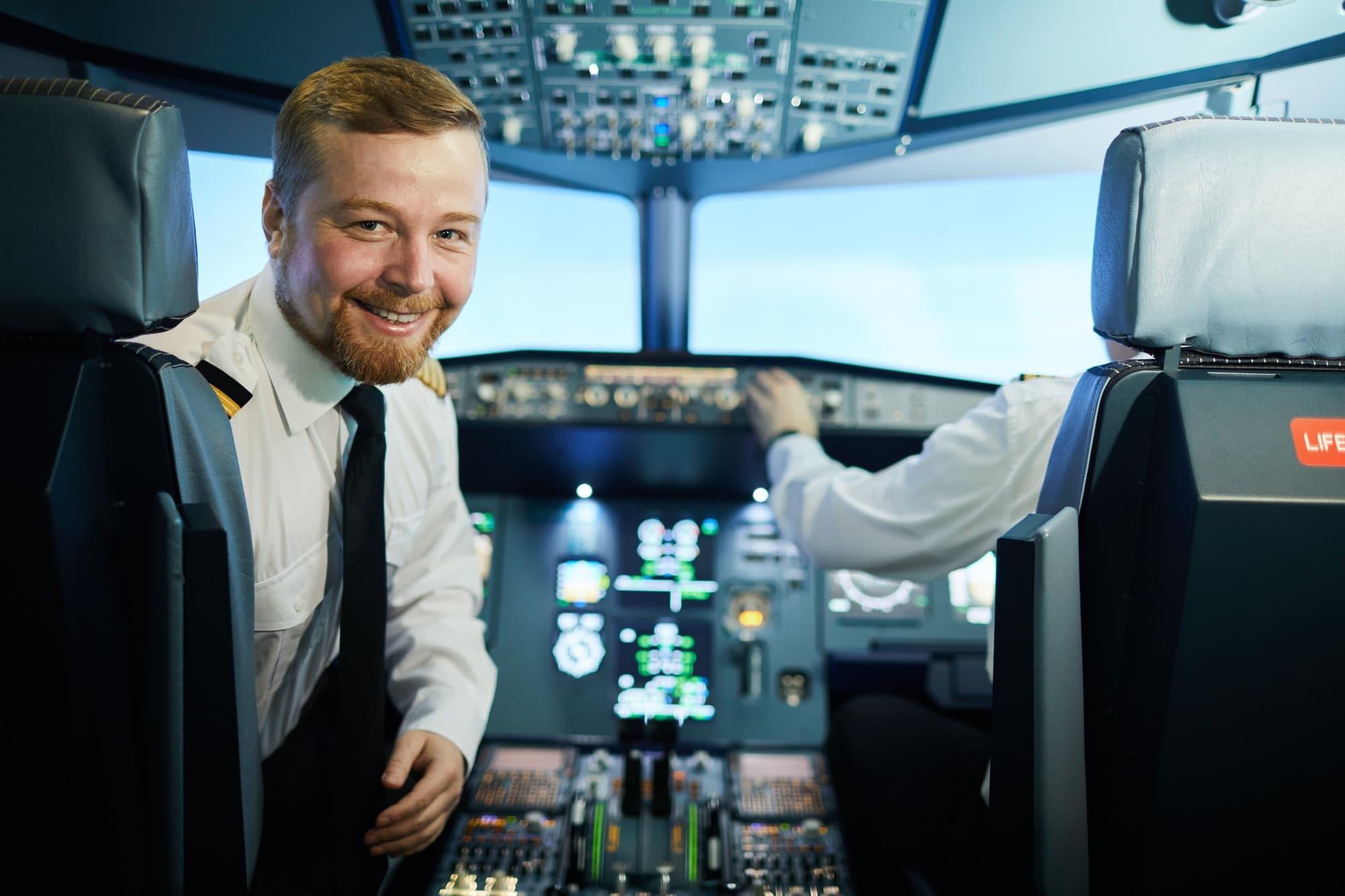 Confident bearded pilot in cockpit